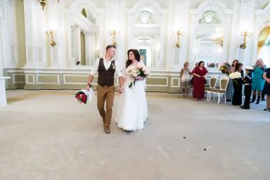 Жених и невеста выходят из за торжественной регистрации брака