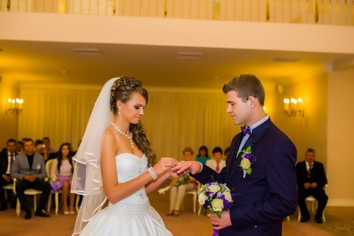 Невеста надевает кольцо на палец жениха