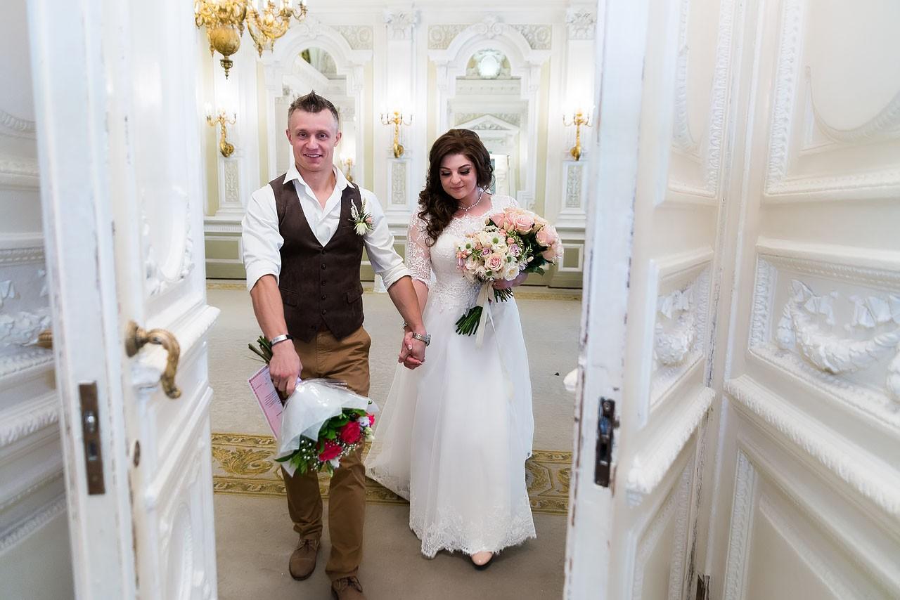 Новоиспеченные муж и жена выходят из зала торжественной регистрации брака