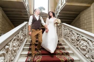 Жених ведёт невесту за руку по лестнице Дворца бракосочетания №1