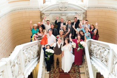 Радостные молодожены и гости после регистрации брака