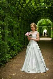 Портрет невесты в зеленом туннеле летнего сада