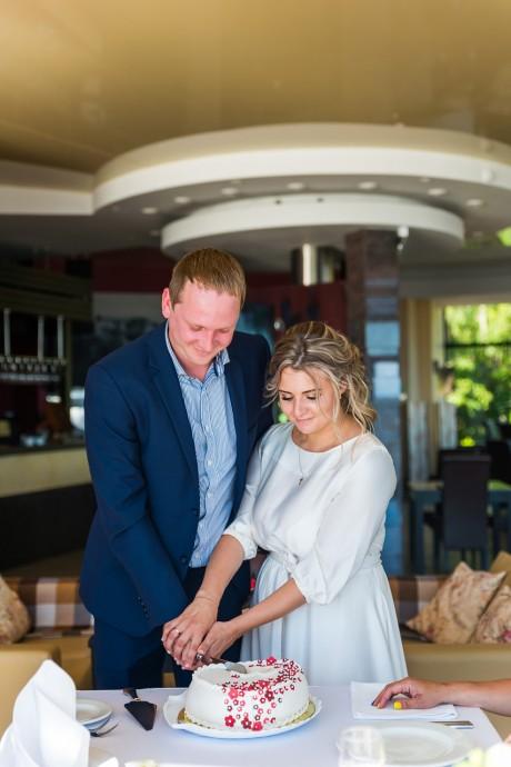 Жених и невеста разрезают свадебный торт на банкете